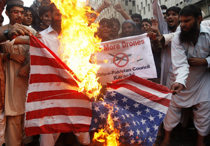 Supporters of Difa-e-Pakistan Council, an Islamic organization, burn U.S. flag during protest against U.S. drone attacks in Pakistani tribal region, in Karachi