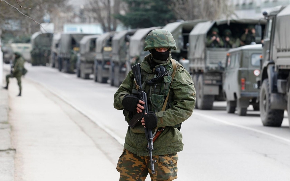 Armed servicemen wait in Russian army vehicles outside a Ukranian border guard post in the Crimean town of Balaclava
