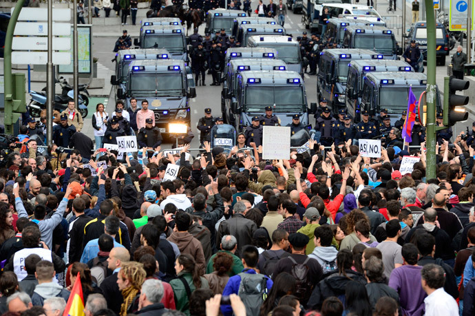 A thousand people gather in front of fences blocking the street leading to the Spain's parliament (Las Cortes) during an anti-government demonstration in Madrid