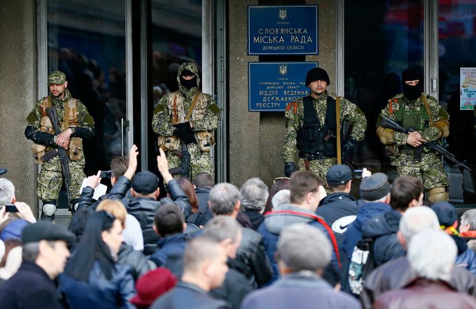 Anti-government armed men stand guard as pro-Russian supporters gather outside the mayors office in Slaviansk April 14, 2014