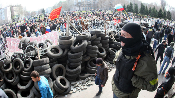 Pro-Russian activists guard a barricade set at the Ukrainian regional Security Service building on the eastern city of Donetsk on April 7, 2014