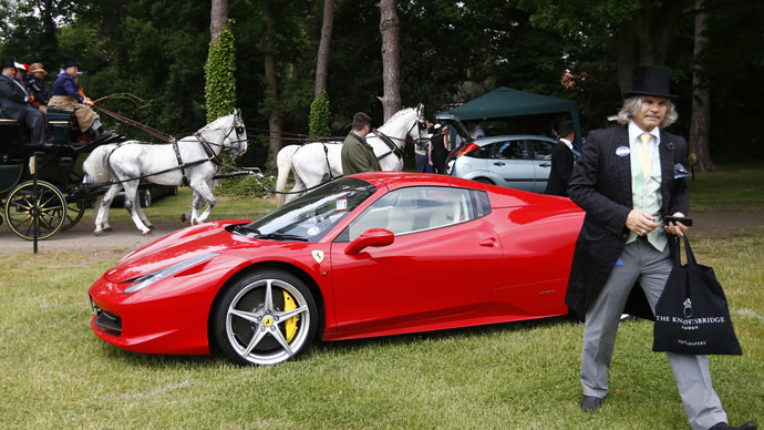 A man walks from his Ferrari as a carriage passes during the fourth day of the Royal Ascot horse racing festival at Ascot, southern England, June 21, 2013.