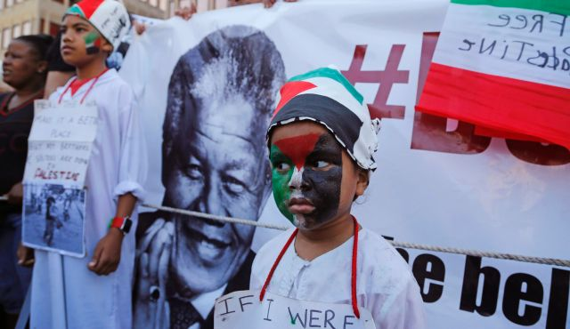 A child next to a picture of Nelson Mandela at a pro-Palestinian rally in Cape Town