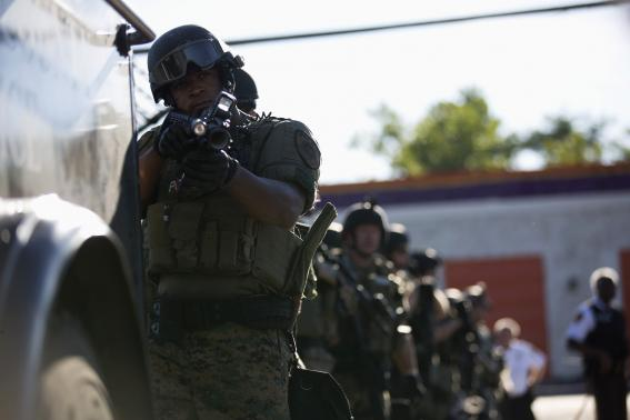 A police officer holds his riot gun while demonstrators protest the shooting death of teenager Michael Brown in Ferguson, Missouri
