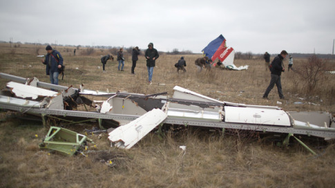 Journalists look at parts of the Malaysia Airlines plane Flight MH17 as Dutch investigators (unseen) arrive at the crash site near the Grabove village in eastern Ukraine