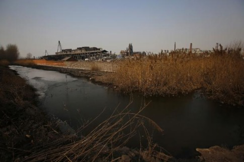 A partially frozen pond is pictured near an abandoned steel mill (back) of Qingquan Steel Group in Qianying township, Hebei province