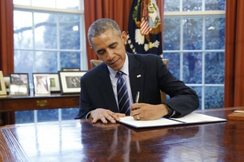Obama signs a presidential memorandum, a Student Aid Bill of Rights to Help Ensure Affordable Loan Repayment, in the Oval Office in Washington