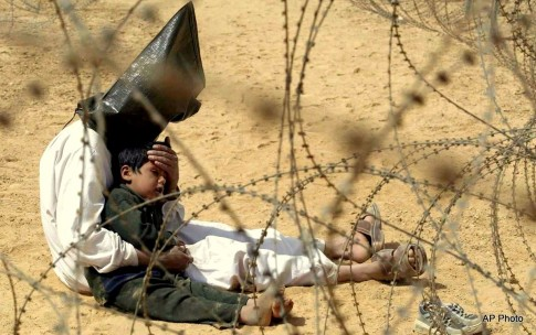 Iraqi prisoner of war comforts his 4-year-old son at a regrouping center for POWs captured by the U.S. Army 101st Airborne Division near An Najaf, Iraq