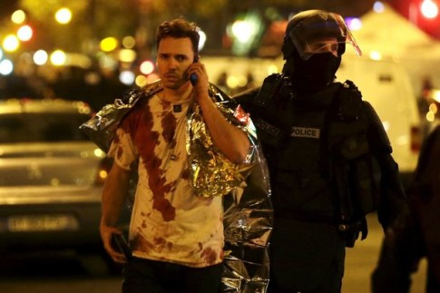 A-French-policeman-assists-a-blood-covered-victim-near-the-Bataclan-concert-hall-following-attacks-in-Paris-France