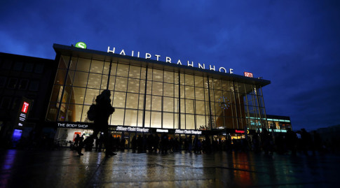 People are silhouetted as they walk past the main railway station in Cologne, Germany