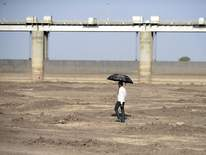 A man walks on a dry reservoir bed next to the Gundar Dam
