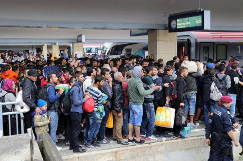 Thousands of newly arrived migrants, the vast majority of whom are men, crowd the platforms at Vienna West Railway Station on August 15, 2015