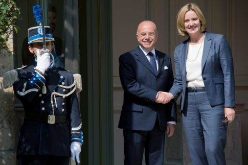 French Interior Minister Bernard Cazeneuve (L) shakes hands with British Home Secretary Amber Rudd