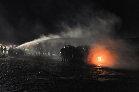 Police use a water cannon to put out a fire started by protesters during a protest against plans to pass the Dakota Access pipeline near the Standing Rock Indian Reservation, near Cannon Ball, North Dakota, U.S. November 20, 2016. REUTERS/Stephanie Keith