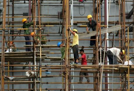 Labourers work on a scaffolding at a construction site in Wuhan