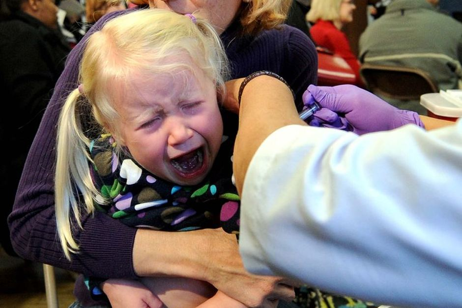 A girl cries as she receives her vaccination