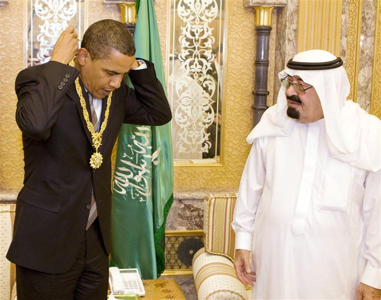 Obama receives a gift from Saudi Arabia's King Abdullah during a meeting at the king's farm outside Riyadh