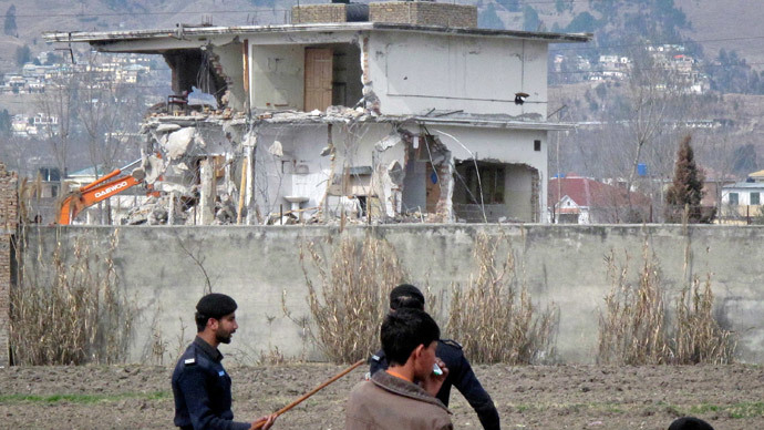 Policemen and residents stand near while demolition work is carried out on the building where al Qaeda leader Osama bin Laden was killed by U.S. special forces in Abbottabad
