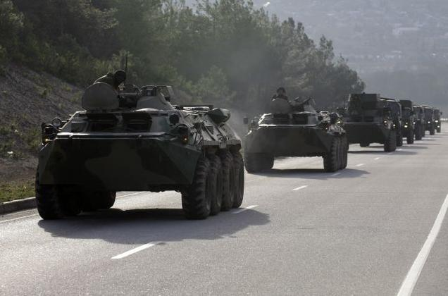 A convoy of military vehicles bearing no license plates travels on the road from Sevastopol to Simferopol, Crimea, Ukraine