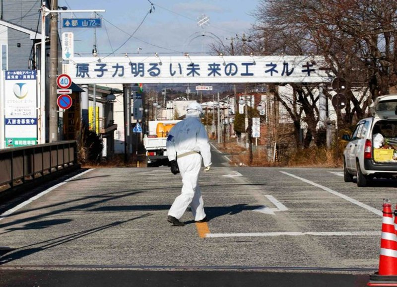 A decontamination worker at the entrance of Futaba, an abandoned town near the Fukushima nuclear plant. The sign proclaims a bright future with nuclear power