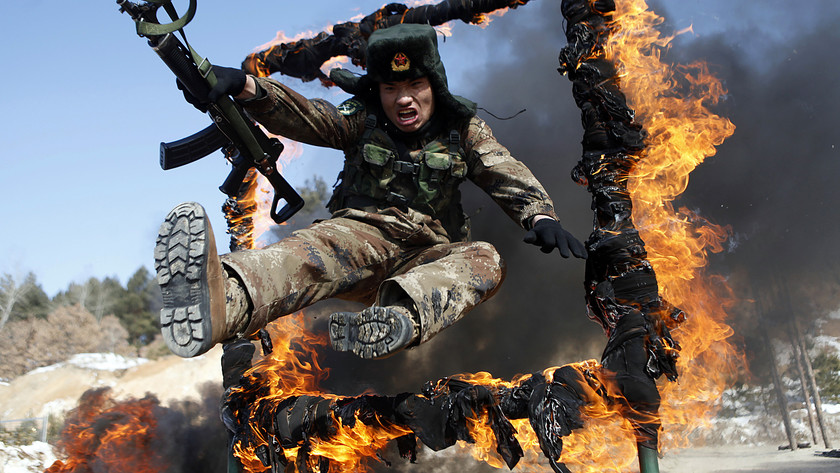 A soldier jumps over a ring of fire during a tactical training mission in Heihe, northeast China's Heilongjiang province, on March 5, 2014