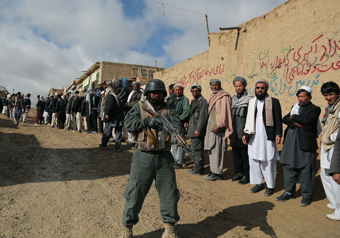 An Afghan policeman keeps watch as Afghan voters line up to vote at a local polling station in Ghazni on April 5, 2014