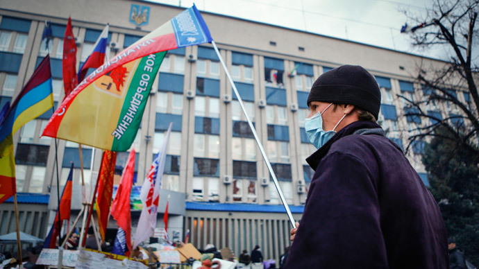An anti-government protester waves a flag in front of the seized office of the SBU state security service in Luhansk, eastern Ukraine April 14, 2014.