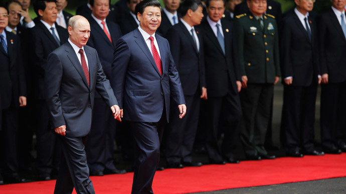 China's President Xi Jinping (front R) walks with Russia's President Vladimir Putin