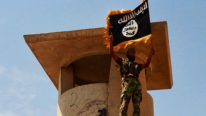 Militant of the Islamic State of Iraq and the Levant (ISIL) posing with the trademark Islamists flag