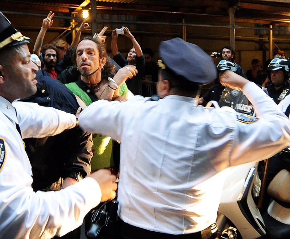 NYPD Deputy Inspector Johnny Cardona (right) hits protester Felix Rivera-Pitre (green shirt), as Occupy Wall Street activists clash with police in the Financial District on Oct. 14, 2011