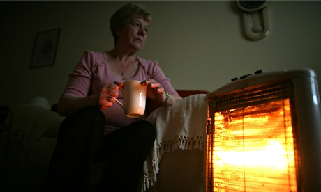 A pensioner sits with an electric heater, Conwy, Wales