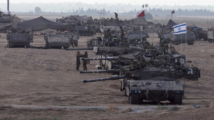 Israeli tanks and armoured personnel carriers (APCs) are seen at a staging area outside the central Gaza Strip July 15, 2014