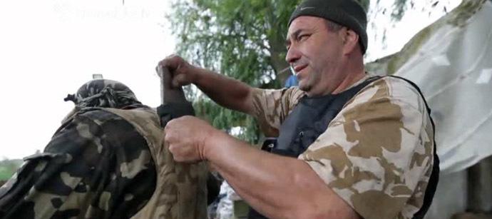 National Guard fighter taking damaged plate from bullet-proof vest. Still from Hromadske.tv video