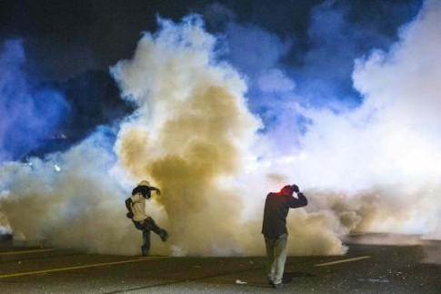 A protester kicks a tear gas canister back towards police after protests in reaction to the shooting of Michael Brown turned violent near Ferguson, Missouri