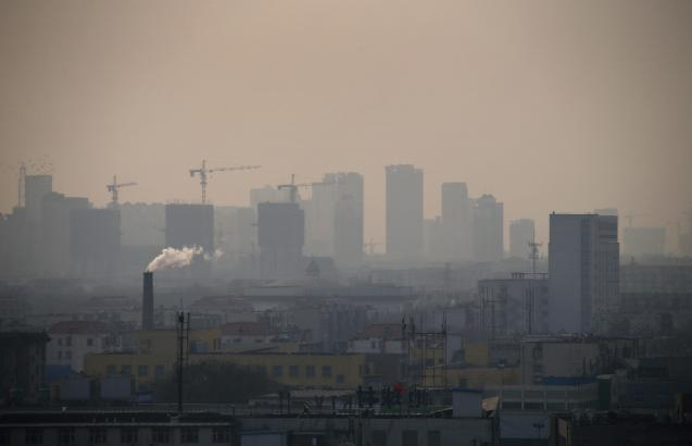 Smoke rises from a chimney among houses as new high-rise residential buildings are seen under construction on a hazy day in the city centre of Tangshan