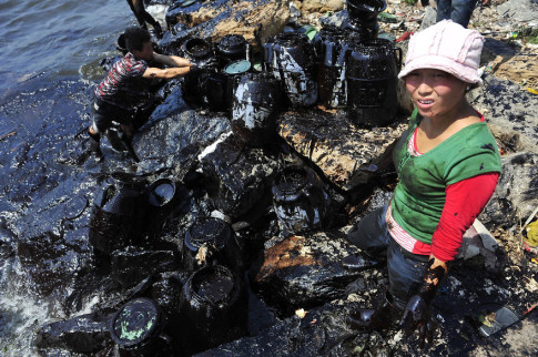 Fishermen clean up oil at an oil spill site near Dalian Port, Liaoning province