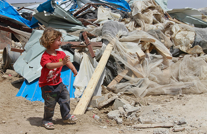 A Palestinian girl walks past her familys house after it was demolished by Israeli bulldozers in Om Ajaj village, north of the West Bank city of Jericho
