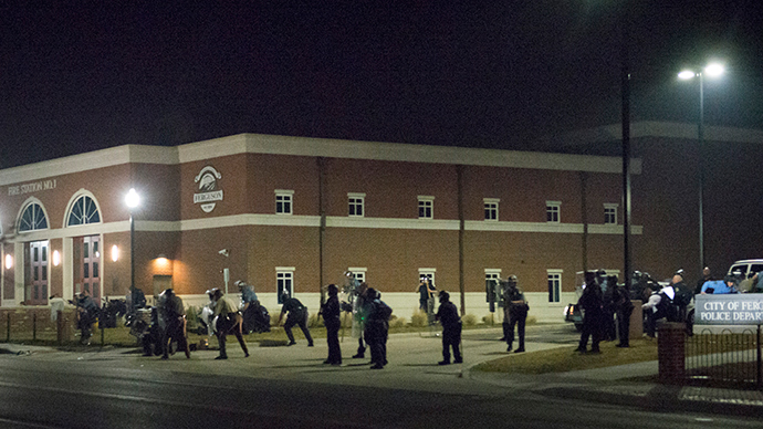 Police stand guard moments after gun shots were fired outside the City of Ferguson Police Department and Municipal Court in Ferguson, Missouri, early March 12, 2015