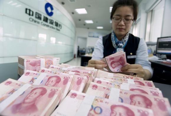 A clerk counts Chinese 100 yuan banknotes at a branch of China Construction Bank in Hai'an, Jiangsu province
