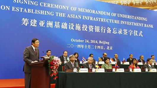 China's Minister of Finance Lou Jiwei, left, delivers a speech next to other representatives of founding member countries at the signing ceremony establishing the Asian Infrastructure Investment Bank in Beijing, Oct. 24, 2014