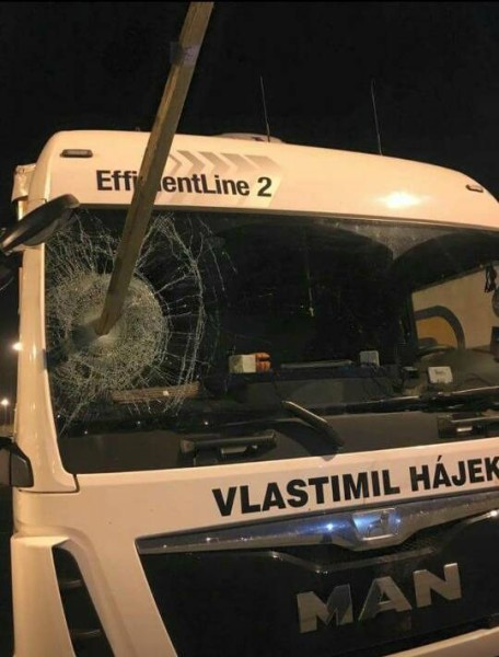A Czech truck driver passing through Calais has narrowly avoided being killed by migrants when they hurled a long wooden stake through the window of his cab before mobbing his vehicle