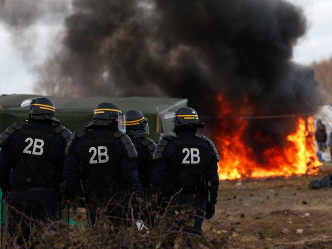 French riot police in front of a burning shelter at the start of the demolition of a part of the Jungle migrant camp in Calais, France, 29 February 2016