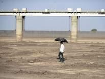 A man walks on a dry reservoir bed next to the Gundar Dam