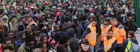 "Migrants line-up to register at a processing centre in the makeshift migrant camp known as ""the jungle"" near Calais, northern France, Monday Oct. 24, 2016"